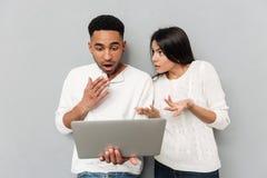 Couples affectueux choqués causant par ordinateur portable Image libre de droits