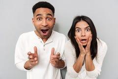 Couples affectueux choqués posant au-dessus du mur gris Photo stock