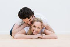 Couples affectueux d'amusement jeunes se trouvant sur le plancher Photos libres de droits