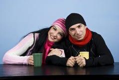 Couples affectueux dans des vêtements de l'hiver buvant du thé Photographie stock