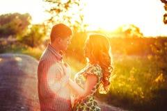 Couples affectueux dans les derniers rayons du soleil sur le champ Photo stock