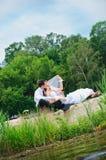 Couples affectueux de mariage se reposant sur le sable près de l'eau Image stock