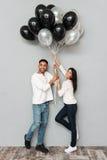 Couples affectueux de sourire tenant des ballons Image libre de droits