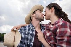 Couples affectueux de style de cowboy emrbacing et embrassant avec des yeux fermés dehors Image libre de droits