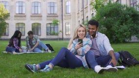 Couples affectueux des étudiants s'asseyant sur la pelouse et la vidéo de observation sur le smartphone clips vidéos