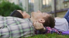 Couples affectueux des ados de métis se trouvant sur la pelouse, appréciant la date Première passion clips vidéos