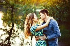 Couples affectueux embrassant au lac dans les bois Image stock