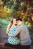 Couples affectueux embrassant se reposer dans les bois Photographie stock libre de droits