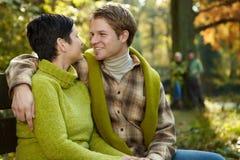 Couples affectueux embrassant sur le banc de stationnement Images stock