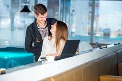 Couples affectueux en café avec l'ordinateur portable Photo stock