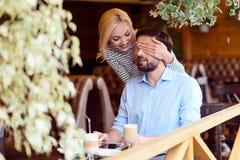 Couples affectueux gais ayant l'amusement dans le cafétéria Photo stock