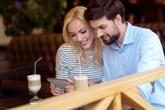 Couples affectueux gais ayant le repos dans le cafétéria Photos libres de droits