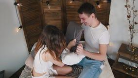 Couples affectueux gais heureux ayant un combat d'oreiller dans le lit et des baisers banque de vidéos