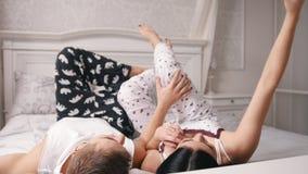 Couples affectueux gais heureux faisant le selfie dans le lit, le jeune type attirant et la fille se situant dans des pyjamas clips vidéos