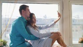 Couples affectueux gais heureux faisant le selfie sur la fenêtre, le jeune type attirant et la fille banque de vidéos