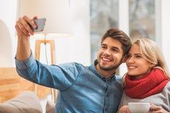 Couples affectueux gais se photographiant sur le smartphone Image libre de droits