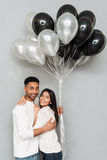 Couples affectueux gais se tenant au-dessus du mur gris avec des ballons Image stock