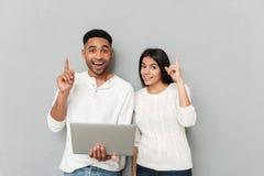 Couples affectueux gais se tenant au-dessus du mur gris et à l'aide de l'ordinateur portable Images libres de droits