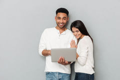 Couples affectueux heureux au-dessus du mur gris causant par l'ordinateur portable Photographie stock libre de droits