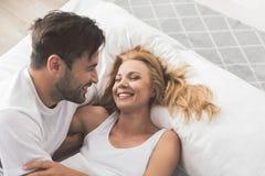 Couples affectueux heureux ayant l'amusement sur la literie Image stock