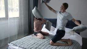 Couples affectueux heureux ayant un combat d'oreiller dans le lit banque de vidéos