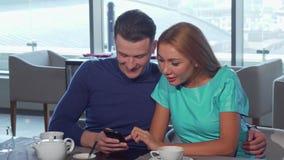 Couples affectueux heureux embrassant, utilisant le téléphone intelligent au café ensemble clips vidéos