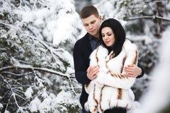 Couples affectueux heureux marchant dans des activités saisonnières extérieures de forêt neigeuse d'hiver Capture de mode de vie Photos stock