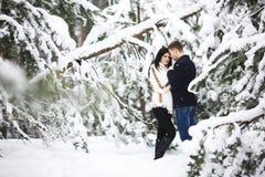 Couples affectueux heureux marchant dans des activités saisonnières extérieures de forêt neigeuse d'hiver Capture de mode de vie Images stock