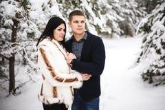 Couples affectueux heureux marchant dans des activités saisonnières extérieures de forêt neigeuse d'hiver Capture de mode de vie Image libre de droits