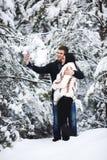 Couples affectueux heureux marchant dans la forêt d'hiver et le selfie neigeux de prise Capture de mode de vie Photo stock