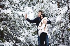 Couples affectueux heureux marchant dans la forêt d'hiver et le selfie neigeux de prise Capture de mode de vie Image libre de droits