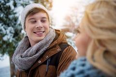 Couples affectueux heureux marchant dans la forêt neigeuse Images stock