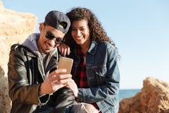 Couples affectueux heureux marchant dehors à la plage causant par le téléphone Images stock