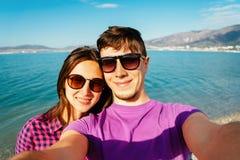 Couples affectueux heureux prenant l'autoportrait sur la plage Photo stock