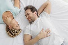 Couples affectueux heureux proliférant sur la literie Image stock