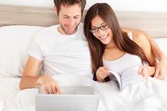 Couples affectueux heureux riant de leur ordinateur portable Photos libres de droits
