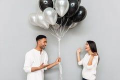 Couples affectueux heureux se tenant au-dessus du mur gris avec des ballons Photographie stock libre de droits