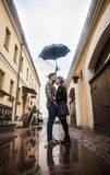 Couples affectueux heureux se tenant sous un parapluie sur une rue de ville un jour pluvieux Image libre de droits