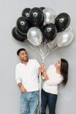 Couples affectueux heureux tenant des ballons Photographie stock