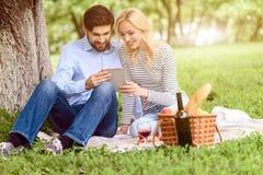 Couples affectueux heureux utilisant l'instrument en nature Photographie stock