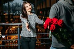 Couples affectueux, homme avec le bouquet de dissimulation des roses derrière le sien de retour Photo stock