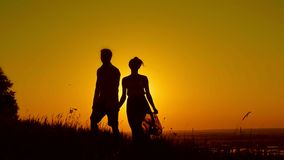 Couples affectueux - jeune homme et belle fille marchant au pré de coucher du soleil - silhouette clips vidéos