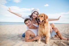Couples affectueux jouant avec leur chien au bord de la mer Images libres de droits