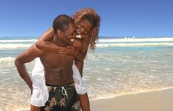 Couples affectueux jouant le long de la plage Image stock