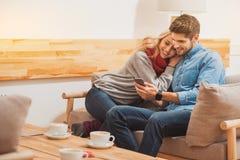 Couples affectueux joyeux se reposant à la maison Image stock
