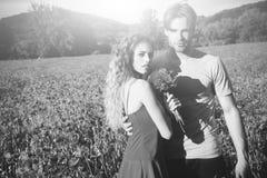 Couples affectueux l'homme et la fille avec le bouquet de fleur dans le pavot rouge mettent en place Photos libres de droits
