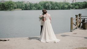 Couples affectueux leur jour du mariage Toilettez est sur un quai, la belle jeune mariée monte à lui, il se tourne vers elle et l banque de vidéos