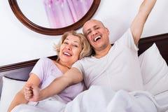Couples affectueux mûrs lounging après avoir réveillé la caresse photos stock