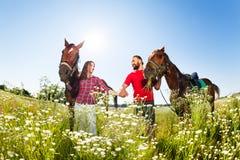 Couples affectueux marchant avec leurs chevaux de race Images libres de droits