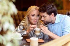 Couples affectueux mignons appréciant la boisson chaude ensemble Image libre de droits